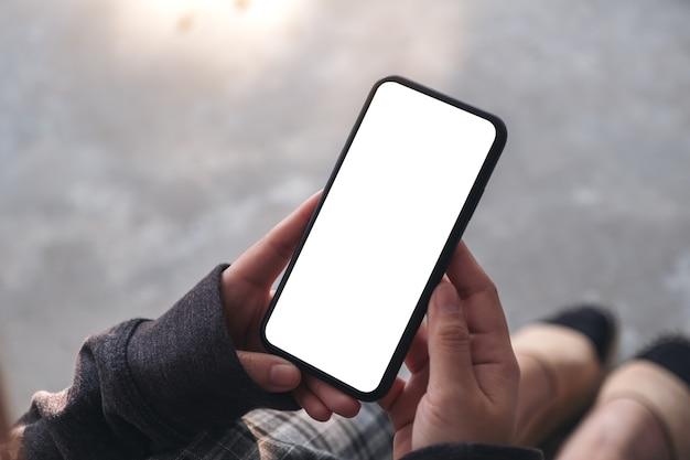 Imagem de maquete de uma mulher segurando um telefone celular preto com uma tela em branco, enquanto está sentada no chão
