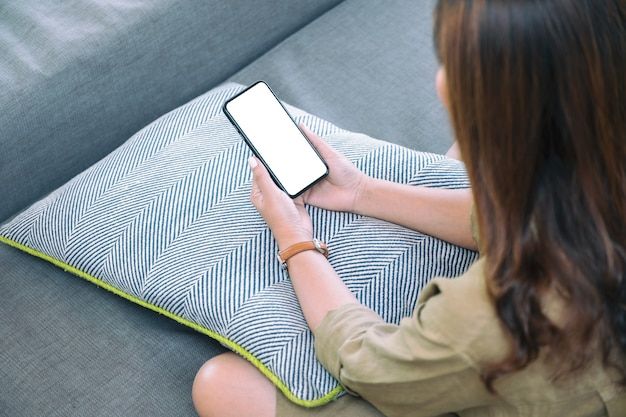 Imagem de maquete de uma mulher segurando um telefone celular preto com uma tela em branco na área de trabalho enquanto está sentada na sala de estar sentindo-se relaxada