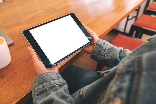 Imagem de maquete de uma mulher sentada e segurando um tablet pc preto com a tela do desktop em branco horizontalmente
