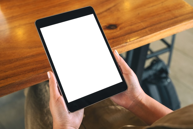 Imagem de maquete de uma mulher sentada e segurando um tablet pc preto com uma tela de desktop em branco