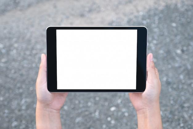Imagem de maquete de vista superior de mãos segurando um tablet pc preto com tela branca em branco
