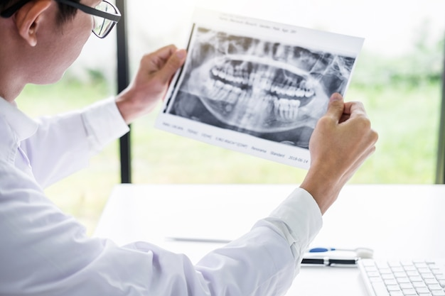 Imagem de médico masculino ou dentista segurando e olhando para raio x dental