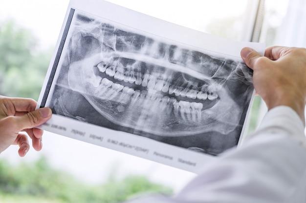 Imagem de médico ou dentista segurando e olhando o raio x