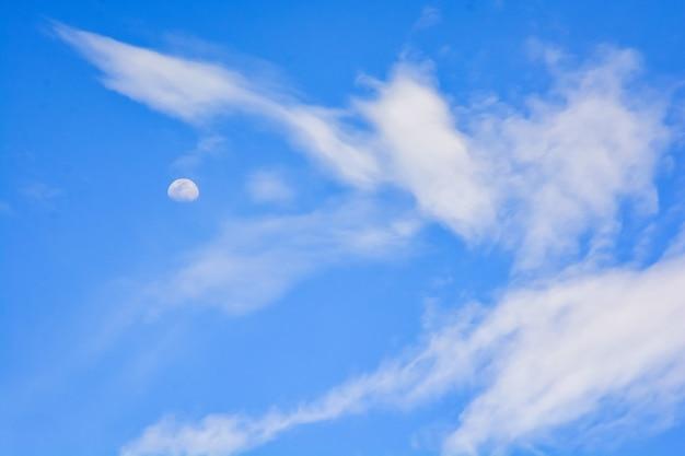 Imagem de meia-lua no céu durante o dia, cercada por lindas nuvens