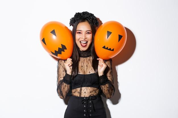 Imagem de menina asiática fantasiada de bruxa malvada segurando dois balões laranja com rostos assustadores