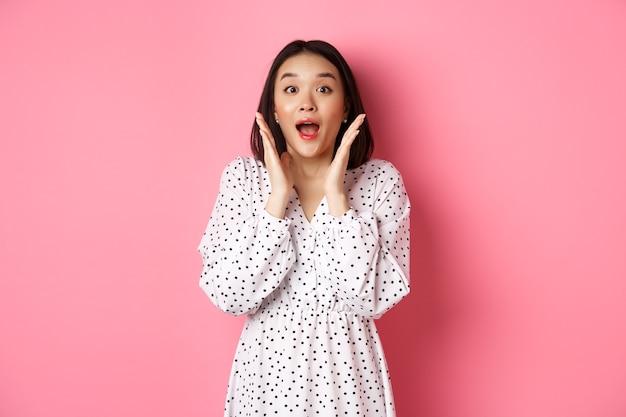 Imagem de menina coreana surpresa em vestido modelo feminino, olhando para a câmera e ofegando amazd em pé ov ...