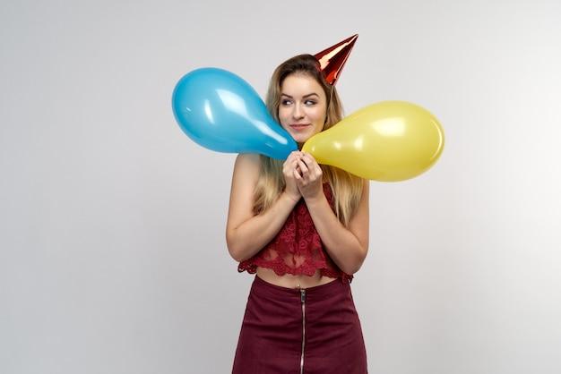 Imagem de menina elegante atraente prepare-se para as férias. loira linda tem bolas coloridas de boné vermelho, vestida com um top vermelho e uma saia cor de vinho.