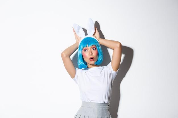 Imagem de menina muito asiática olhando surpresa para a esquerda, usando peruca azul e orelhas de coelho para a festa de halloween, em pé.