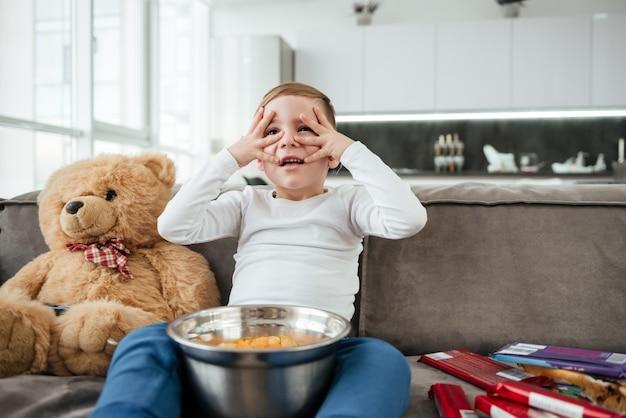 Imagem de menino assustado no sofá com o ursinho de pelúcia em casa assistindo tv enquanto come batatas fritas.