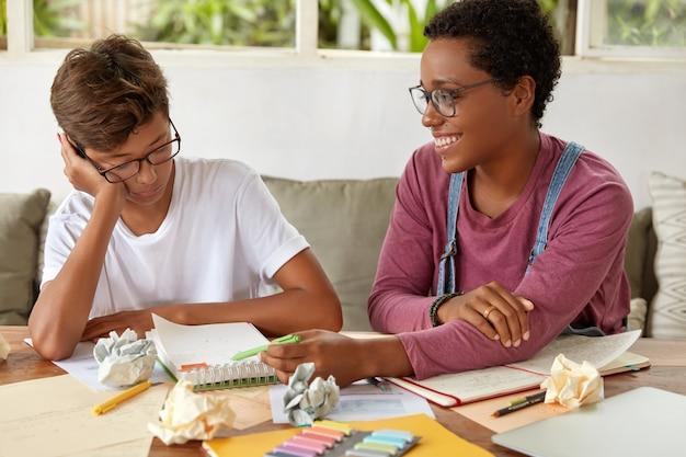 Imagem de menino e menina mestiços colaboram na preparação do trabalho do curso, anotam no bloco de notas, sentam no sofá, trabalham na apresentação para a aula, sendo equipe conceito de aprendizagem e colaboração