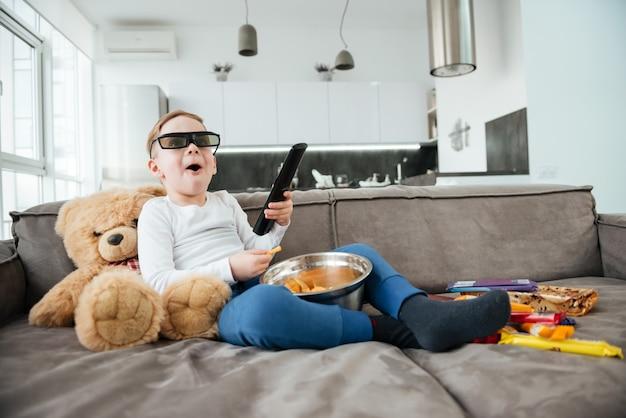 Imagem de menino no sofá com o ursinho de pelúcia em casa assistindo tv com óculos 3d enquanto come batatas fritas. segurando o controle remoto.
