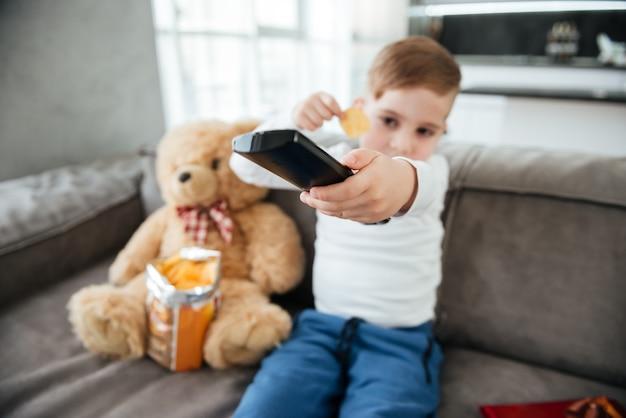 Imagem de menino sentado no sofá com o ursinho de pelúcia em casa e assistindo tv enquanto come batatas fritas. segurando o controle remoto. concentre-se no controle remoto.