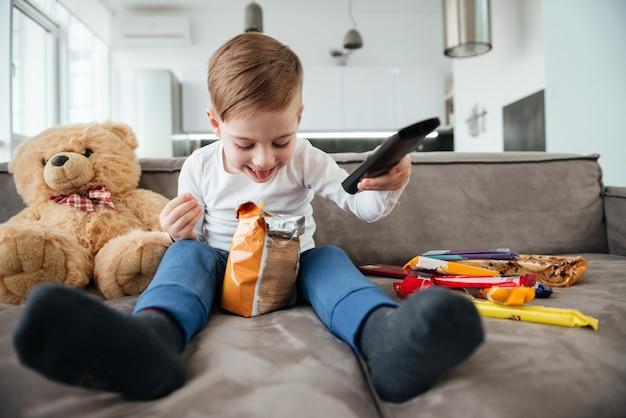 Imagem de menino sentado no sofá com o ursinho de pelúcia em casa e assistindo tv enquanto come batatas fritas. segurando o controle remoto.