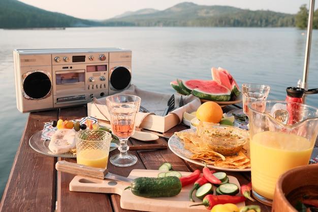 Imagem de mesa de jantar com salgadinhos de frutas e sucos na festa em um píer ao ar livre