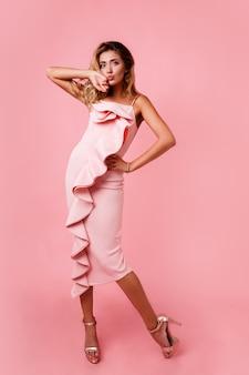 Imagem de moda altura total da mulher loira com penteado ondulado perfeito no vestido de festa rosa posando. saltos altos. cara de surpresa. espaço para texto.