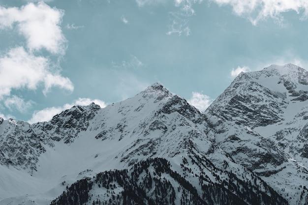 Imagem de montanhas rochosas cobertas de neve sob um céu nublado e luz do sol