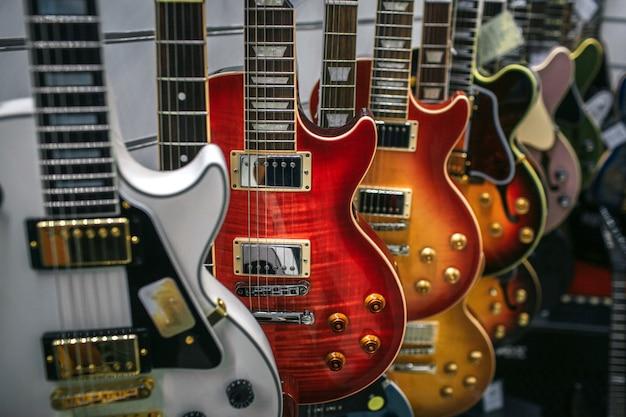 Imagem de muitas guitarras eletrônicas penduradas. são cores e formas diferentes.