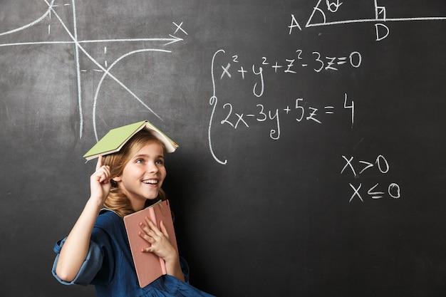 Imagem de muito feliz menina da escola jovem posando isolado sobre a parede da parede do quadro-negro.