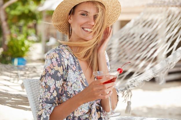 Imagem de mulher adorável usa camisa e chapéu de verão, recria ao ar livre com coquetel, descansa no bar da praia, se diverte com expressão feliz bela jovem curtindo o verão
