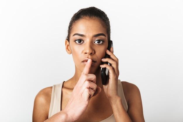 Imagem de mulher africana posando falando por telefone celular enquanto a mão de alguém mostrando o gesto de silêncio.