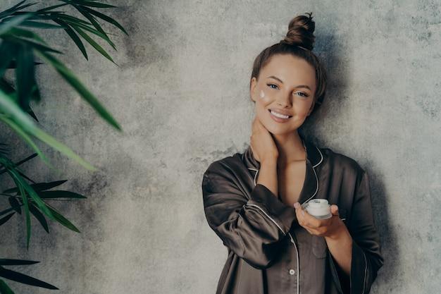 Imagem de mulher alegre em pijama de seda sorrindo ao aplicar creme facial, posando com um frasco de loção hidratante na mão, isolado sobre o fundo da parede de concreto. conceito de beleza e cuidados com a pele