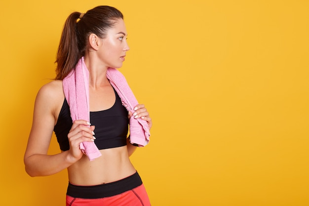 Imagem de mulher atlética com uma toalha rosa nos ombros