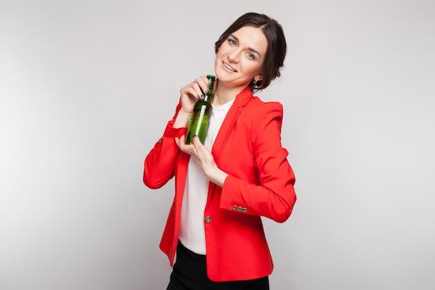 Imagem de mulher atraente vestido vermelho com cerveja verde nas mãos