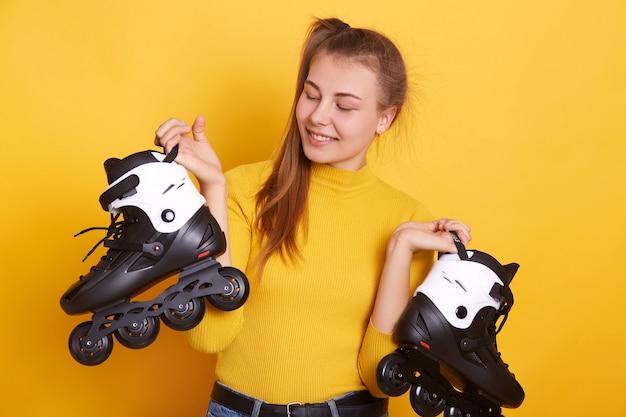 Imagem de mulher bonita com patins nas mãos, estar de bom humor