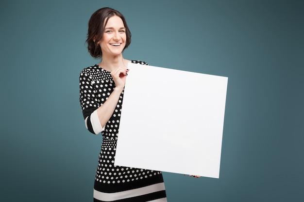 Imagem de mulher bonita em roupas manchadas de pé com papel grande nas mãos