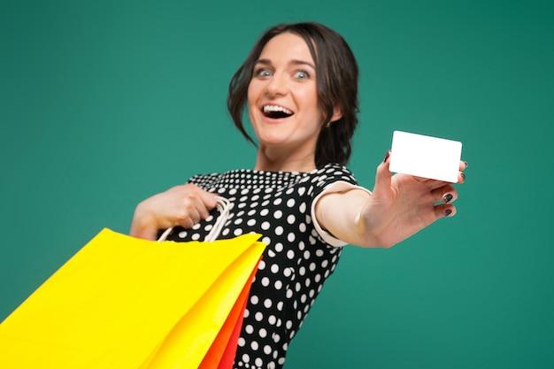 Imagem de mulher bonita em roupas salpicadas de pé com compras e fraque nas mãos