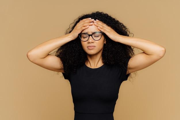 Imagem de mulher bonita se sente mal, toca a testa, sofre de dor de cabeça, fecha os olhos de dor