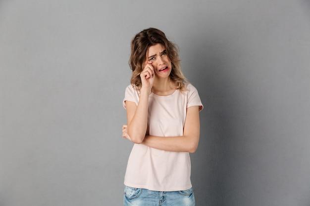 Imagem de mulher chateada em t-shirt chorando sobre cinza