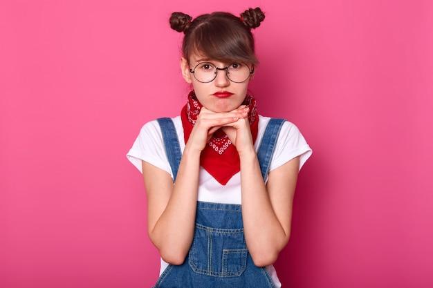 Imagem de mulher chateada europeia com cabelos escuros e cachos, usa macacão, camiseta e bandana. garota adorável estar de mau humor enquanto posava sozinha, mantém as mãos sob o queixo. conceito de adolescente.