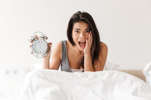 Imagem de mulher chocada acordando e se atrasando, segurando o despertador tocando em pânico Foto Premium