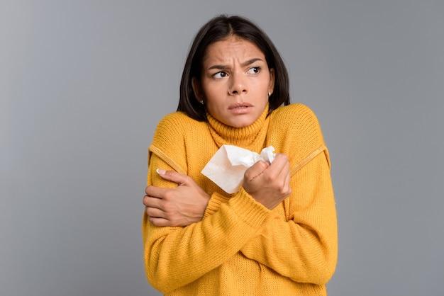 Imagem de mulher congelada doente isolado sobre a parede cinza segurando o guardanapo.