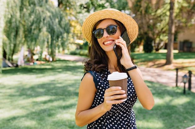 Imagem de mulher de estilo encantador está caminhando no parque de verão com chapéu de verão e óculos de sol pretos e vestido bonito. ela bebe café e fala ao telefone com grandes emoções.