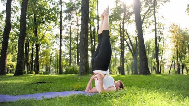 Imagem de mulher de meia idade sorridente com roupas de fitness, fazendo alongamento e exercícios de ioga. mulher meditando e praticando esportes na esteira de ginástica na grama do parque