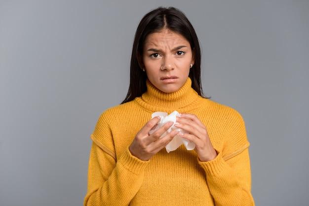 Imagem de mulher doente em pé isolada sobre a parede cinza segurando o guardanapo.