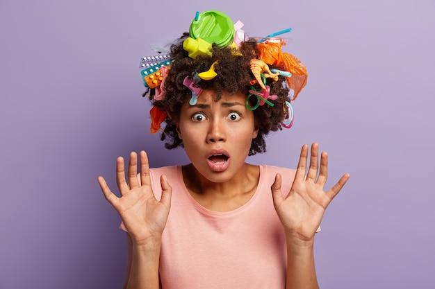 Imagem de mulher encaracolada atônita coleta lixo plástico, levanta as mãos e mostra as palmas das mãos, com medo de desastres naturais, tem sujeira no cabelo, abre a boca de tanto engasgar. ecologia, voluntariado e caridade