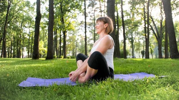 Imagem de mulher feliz sorridente de meia idade meditando e fazendo exercícios de ioga na grama na floresta. mulher cuidando de sua saúde física e mental enquanto pratica exercícios físicos e alongamento no parque