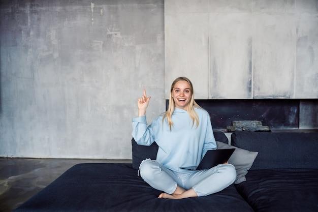 Imagem de mulher feliz usando laptop prata enquanto está sentado no sofá