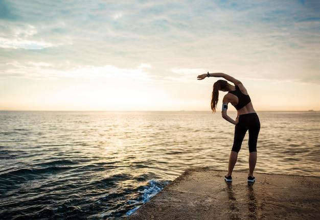 Imagem de mulher jovem bonita fitness faz exercícios de esporte
