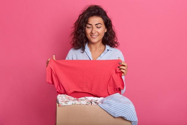 Imagem de mulher jovem e alegre sorrindo sinceramente e segurando uma camisa vermelha nas mãos