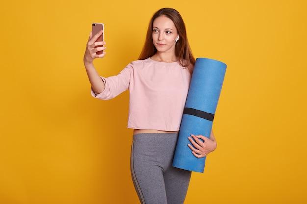Imagem de mulher jovem e ativa cabelos escuros posando com tapete de ioga azul.