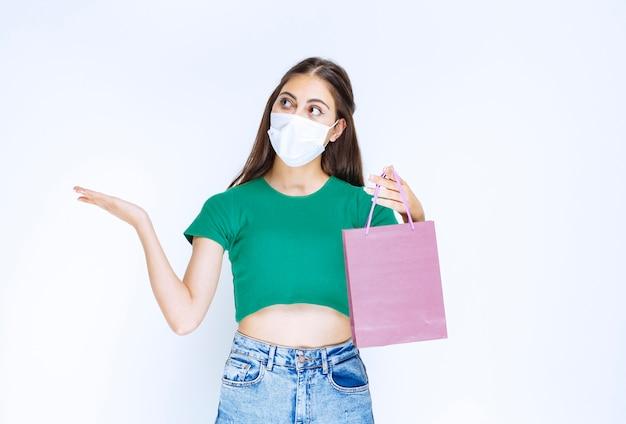 Imagem de mulher jovem e bonita na máscara médica segurando uma bolsa roxa.
