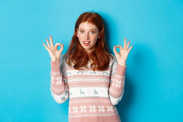 Imagem de mulher jovem ruiva confiante mostrando sinais de ok, garantir tudo de bom, elogiando a escolha, em pé sobre um fundo azul.