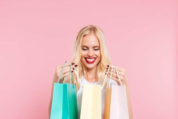 Imagem de mulher loira satisfeito olhando pacotes sobre rosa