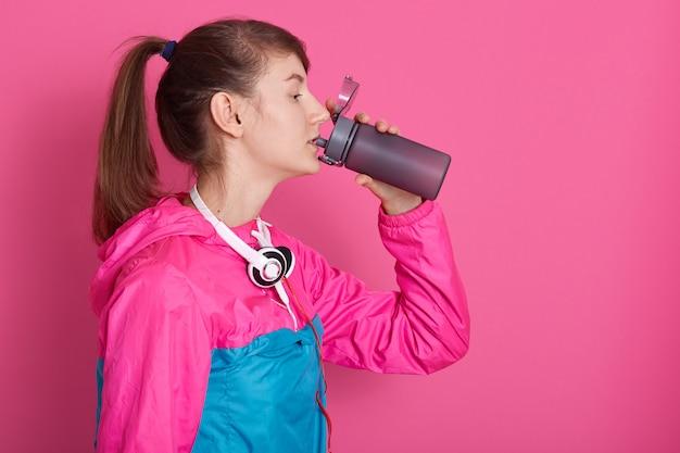 Imagem de mulher morena atraente com água potável de ponitail