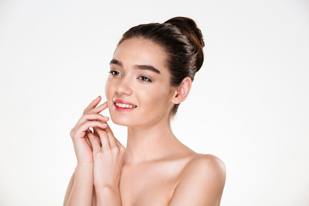 Imagem de mulher morena com cabelos em coque e maquiagem natural, sorrindo e olhando de lado