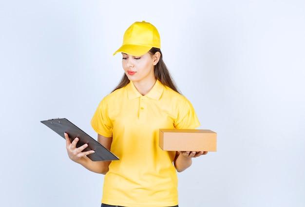 Imagem de mulher positiva segurando o pacote e a área de transferência sobre a parede branca.